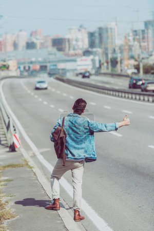 Photo for Back view of man hitchhiking alone on road - Royalty Free Image