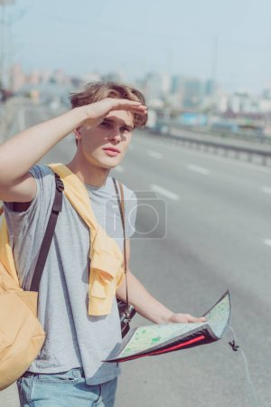 Photo for Young man with map and backpack looking for destination - Royalty Free Image