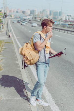 young man with map and backpack looking for destination
