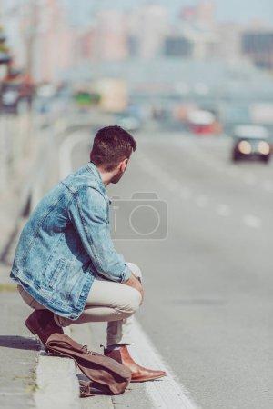 Photo pour Vue partielle de l'homme assis sur la route - image libre de droit