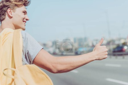 Photo for Smiling young man hitchhiking on road - Royalty Free Image
