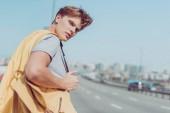 vue arrière du jeune homme, faisant de l'auto-stop sur route