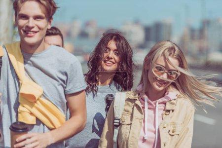 Foto de Vista parcial de sonrientes jóvenes viajeros caminando en la calle mientras viajan juntos - Imagen libre de derechos