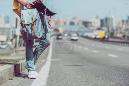 cropped shot of tourist with map and backpack standing on road