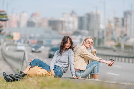Photo for Female travelers resting on green grass during trip in new city - Royalty Free Image