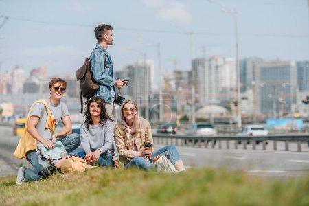 Foto de Grupo de jóvenes viajeros con mochilas en ciudad nueva - Imagen libre de derechos