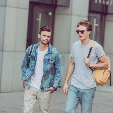 Photo for Portrait of young travelers with backpacks walking on city street - Royalty Free Image