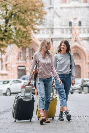 Photo for Female tourists with backpacks and baggage walking on city street - Royalty Free Image