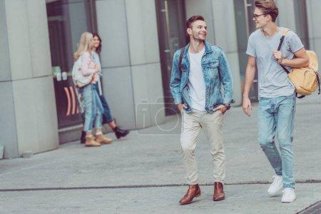 Photo pour Jeunes voyageurs avec sacs à dos, marchant sur la rue de la ville - image libre de droit