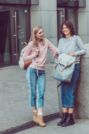 Photo for Attractive women with backpacks on city street during journey - Royalty Free Image