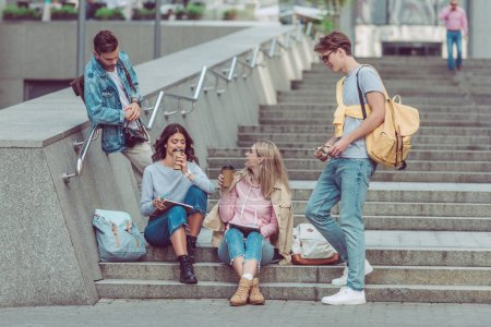 Photo for Friends resting on street steps in new city - Royalty Free Image