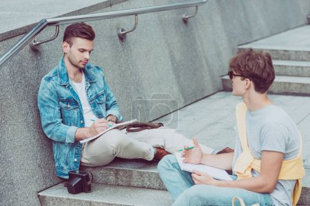 Photo for Young men with notebooks sitting on city steps in new city - Royalty Free Image
