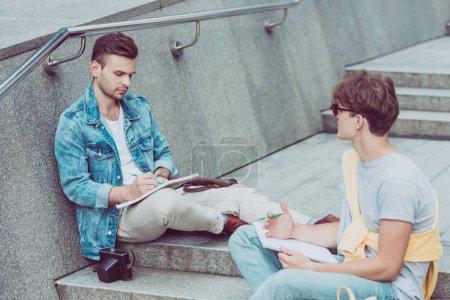 Photo pour Jeunes hommes avec les ordinateurs portables, assis sur les marches de la ville dans la ville de new - image libre de droit