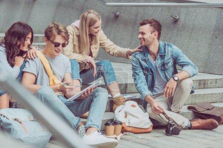 turistas jóvenes descansando en los escalones en la calle de la nueva ciudad