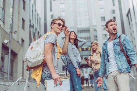 Photo for Group of young tourists with backpacks standing on street in new city - Royalty Free Image