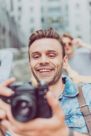 Photo for Selective focus of smiling man with photo camera traveling in new city - Royalty Free Image