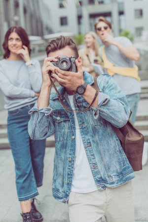 selective focus of tourist taking picture on photo camera with friends behind on street