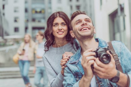 smiling couple of tourists holding photo camera in city with friends behind
