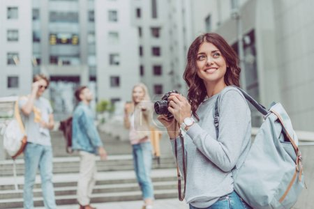 smiling female photographer with camera walking in city with friends