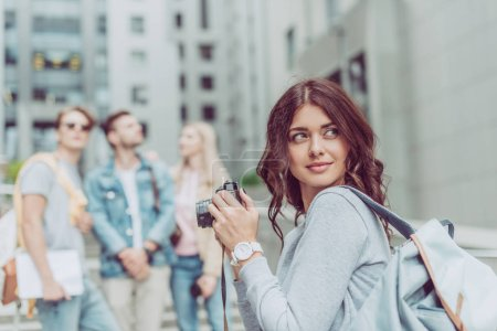 beautiful female photographer with camera in city with friends
