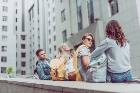young stylish couples on travelers talking and sitting in urban city
