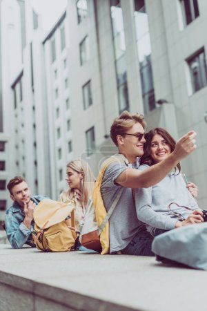 young beautiful couples sitting in city, while smiling man showing something
