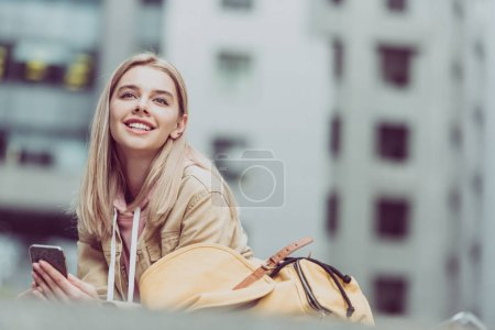 happy young blonde woman with backpack using smartphone in city