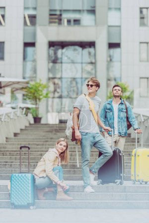 Photo for Stylish tourists with backpacks and travel suitcases on stairs in city - Royalty Free Image