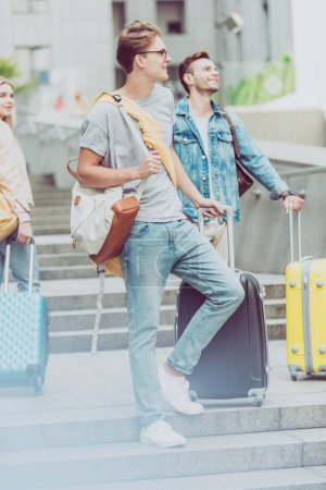 young stylish friends with backpacks and travel bags on stairs