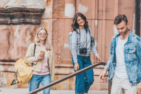 Foto de Amigos jóvenes con mochilas pasar tiempo juntos en la ciudad de - Imagen libre de derechos
