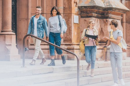 young tourists with map walking in city