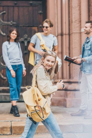 smiling blonde girl with photo camera in city with friends