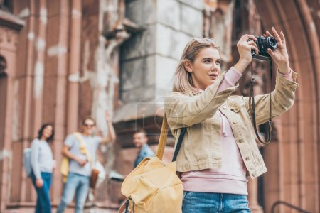 attractive girl taking photo of city on camera with friends behind