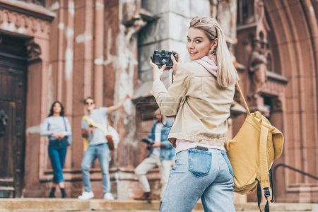 happy girl taking photo of friends on camera in city