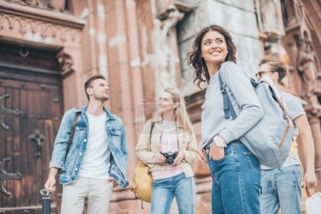 Photo for Young smiling tourists spending time together in city - Royalty Free Image