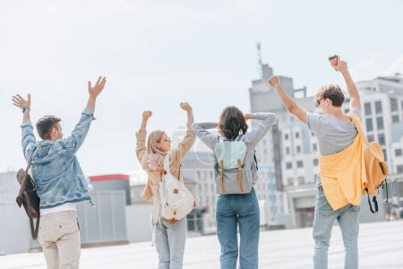 back view of young stylish tourists gesturing having fun and walking in city