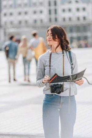 Photo pour Touristique femelle avec appareil photo et carte de ville - image libre de droit