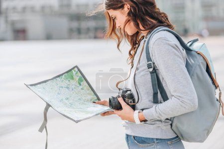female traveler with photo camera looking at map in city