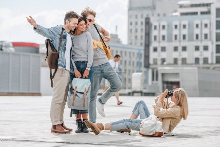 girl sitting on street and taking photo of cheerful travelers in city