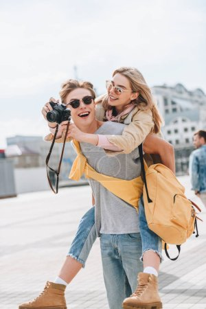 happy boyfriend giving piggyback to girlfriend with photo camera in city