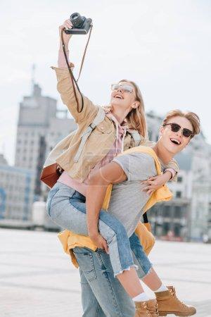 cheerful boyfriend piggybacking girlfriend while she taking photo on camera