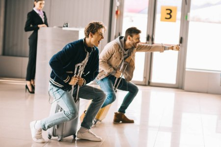 Photo for Happy young men having fun and riding suitcases in airport - Royalty Free Image