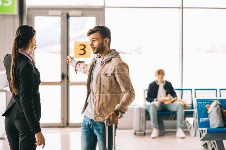 Photo pour Travailleuse, montrant les portes au jeune homme avec valise à l'aéroport - image libre de droit