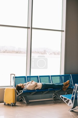 young man lying on seats while waiting for flight in airport terminal