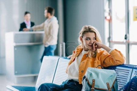 Photo pour Souriante jeune femme avec sac à dos s'asseoir et regarder loin dans le terminal de l'aéroport - image libre de droit