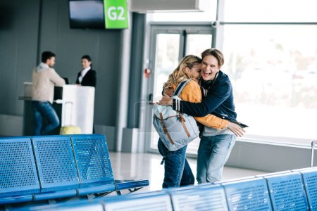Photo for Excited young couple with backpacks hugging in airport terminal - Royalty Free Image