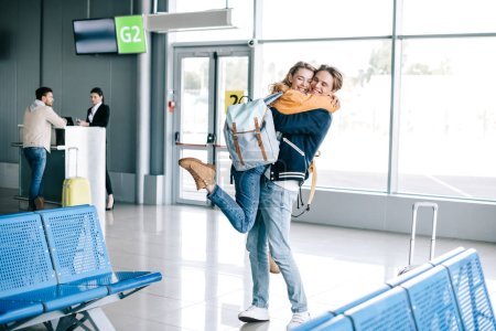cheerful young couple hugging in airport terminal