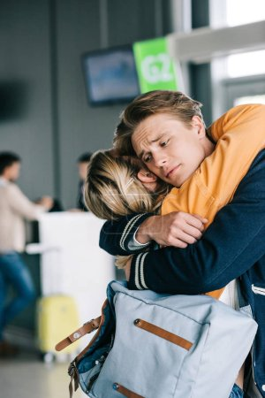 Photo for Close-up view of emotional young couple hugging in airport terminal - Royalty Free Image