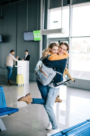 Photo for Cheerful young couple of travelers hugging in airport terminal - Royalty Free Image