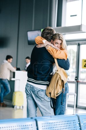 emotional young couple hugging in airport terminal